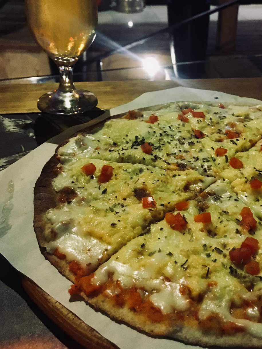 pizza de seis fatias e copo de chope em ilhabela